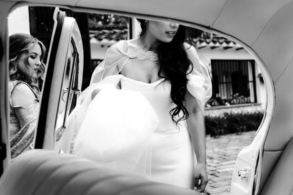 A black and white photo of a bride walking up to the getaway car